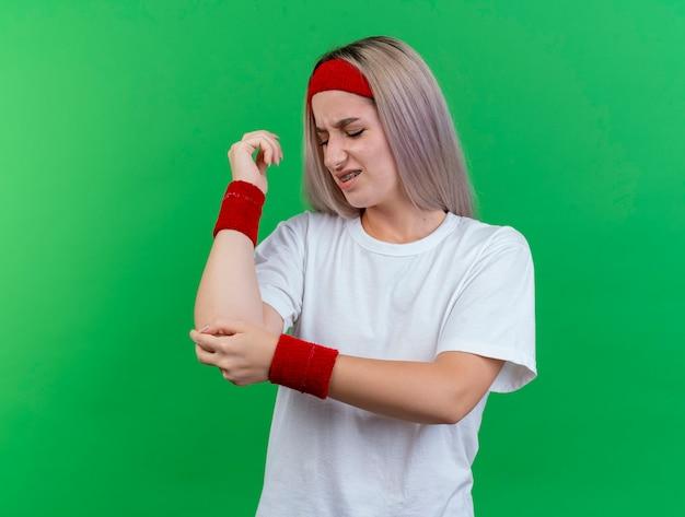 Dolorante giovane donna sportiva con le parentesi graffe che indossa la fascia e braccialetti mette la mano sul gomito isolato sulla parete verde