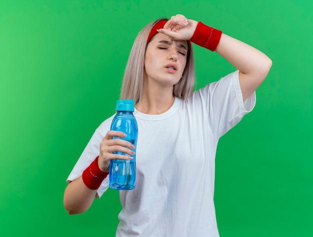 Giovane donna sportiva dolorante con bretelle che indossa fascia e braccialetti mette la mano sulla fronte e tiene la bottiglia d'acqua isolata sulla parete verde