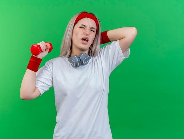 Giovane donna sportiva dolorante con bretelle che indossa fascia e braccialetti con le cuffie sul collo mette la mano sul collo dietro e tiene il manubrio isolato sulla parete verde