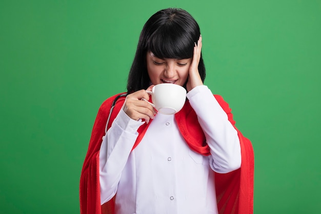 Aching young superhero girl wearing stethoscope with medical robe and cloak drinks tea putting hand on head isolated on green wall