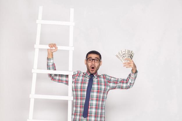 キャリアの成功を達成する!青いネクタイが立って、現金と白い階段のお祝いのファンを保持しているカラフルな市松模様のシャツを着た金持ちのハンサムなひげを生やした男。屋内、スタジオショット、灰色の背景に分離
