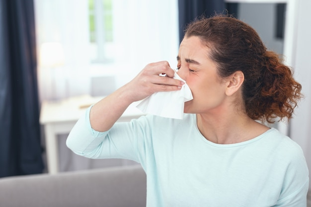 Achoo once more. lady on a sick leave staying at home and having a runny nose as a result of suffering from a sudden burst of seasonal allergies