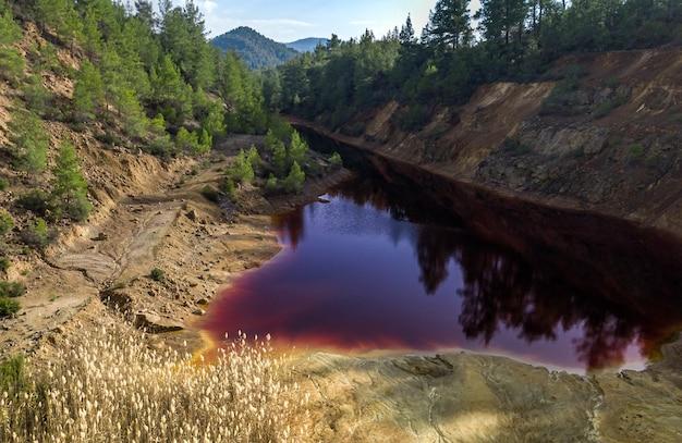 숲에 버려진 노천 광산에서 산성 붉은 호수