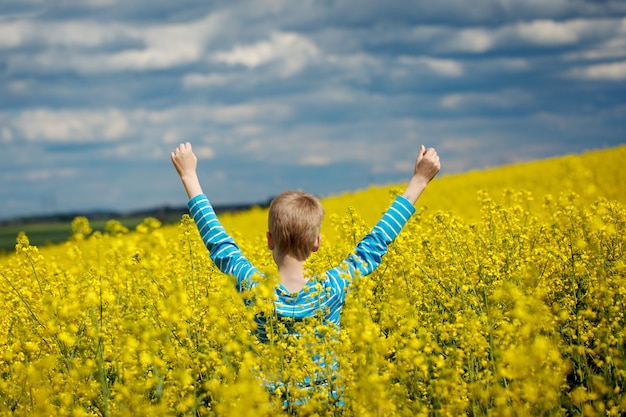 Ack view. happy smiling  boy jumping for joy on a yellow field