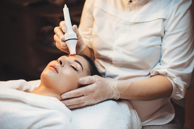 Acne treatment procedures done to a woman lying on a couch in spa center during beauty sessions