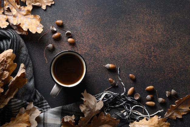 Желудь кофе в уютном образе жизни на коричневом столе с осенними дубовыми листьями и уютным шарфом. концептуальный заменитель кофе без кофеина. вид сверху. место для текста.