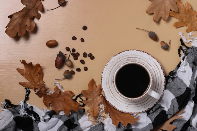Acorn coffee with fall oak leaves and checkered scarf on beige background.