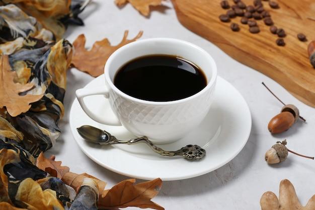灰色の背景に秋のオークの葉とどんぐりコーヒー。カフェインを含まないコーヒー代用品。