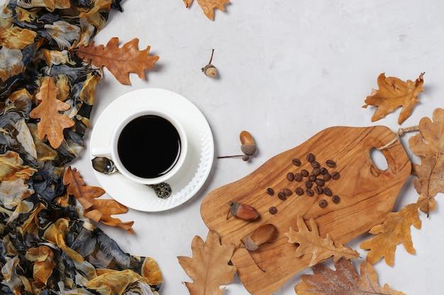 灰色の表面に秋のオークの葉とどんぐりコーヒー