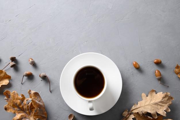 Желудь кофе с дубовыми листьями на сером бетонном столе