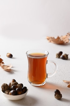 白いテーブルの上にオークの葉とどんぐりコーヒー。閉じる。テキスト用のスペース。