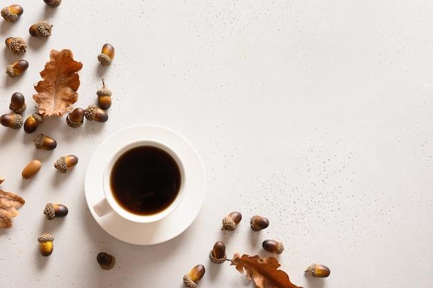 白いテーブルの上にオークの葉とどんぐりコーヒー。上からの眺め。テキスト用のスペース。
