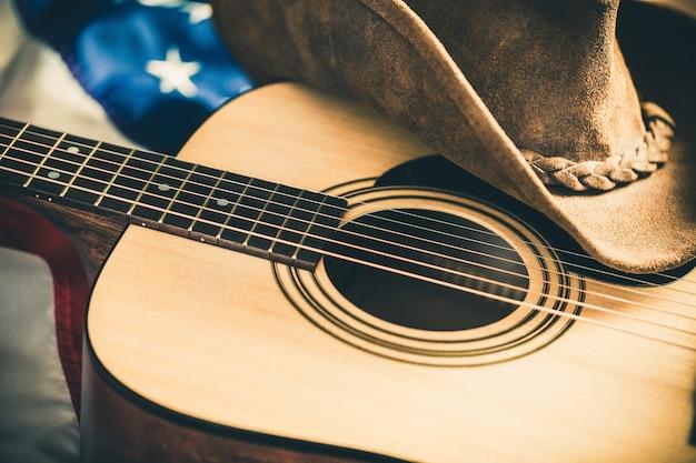 Акустическая гитара и ковбойская шляпа с американским флагом на фоне