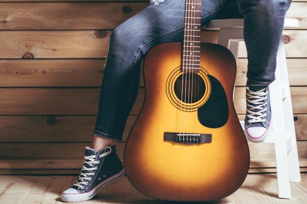 Акустическая гитара и ноги женщины, сидящей на стуле в джинсах