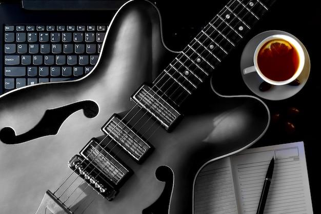 自宅での日記オンラインギターレッスン付きのアコースティックギターとノートブック。フラットレイ