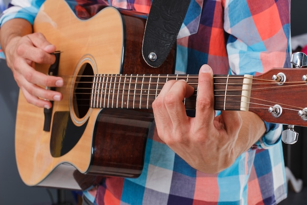 Играют на акустической гитаре. пальцы держат гриф. мужская рука держит гриф.
