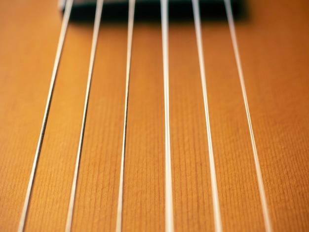 사운드 홀 배경이 없는 어쿠스틱 기타 바디. 갈색 나무 일렉트릭 기타에 있는 6개의 현을 닫습니다.