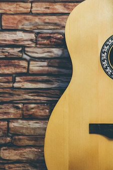 Acoustic guitar on a brick wall background.