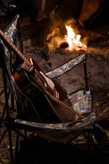 Acoustic guitar in camping chair with fire flame on background. summer camping. relaxation in nature. vertical image. high iso