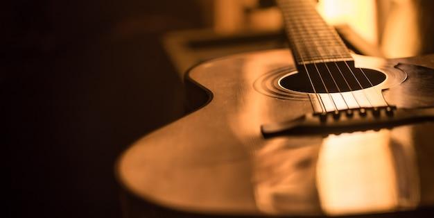 美しい色の背景上のアコースティックギターのクローズアップ