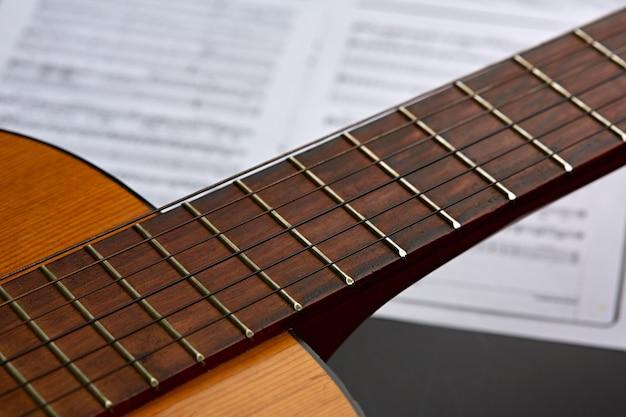 Гриф для акустической гитары, нотная тетрадь, никто. концепция струнного музыкального инструмента, живой звук, оборудование для музыкантов