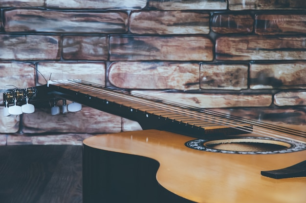 Acoustic guitar lies on a wooden table against a brick wall. side view.