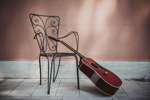 Acoustic guitar lying in front of the house with empty chair, vintage style