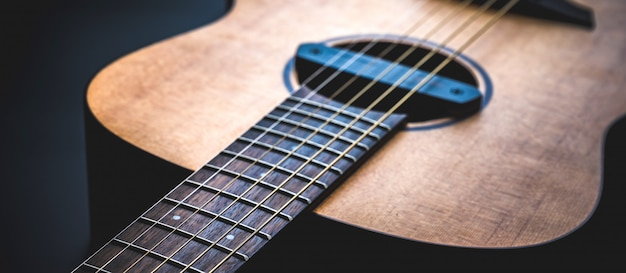 Acoustic guitar, music instrument resting against a dark black wall with copy space, close-up of wooden classic guitar