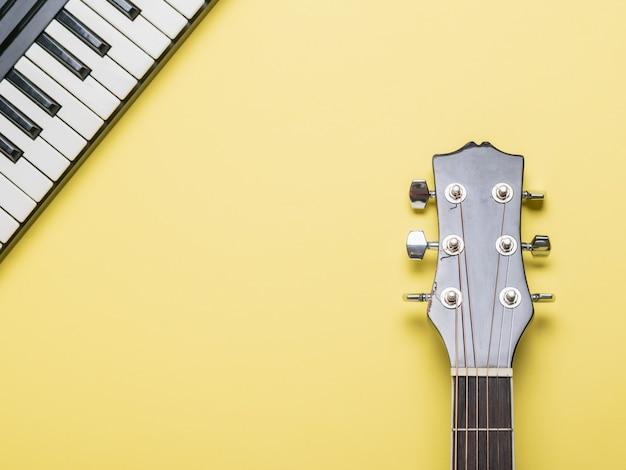 Шея акустической гитары и клавиши пианино на желтой поверхности