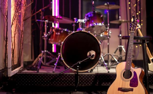 Акустическая гитара на столе студии звукозаписи. понятие о музыкальном творчестве и шоу-бизнесе.