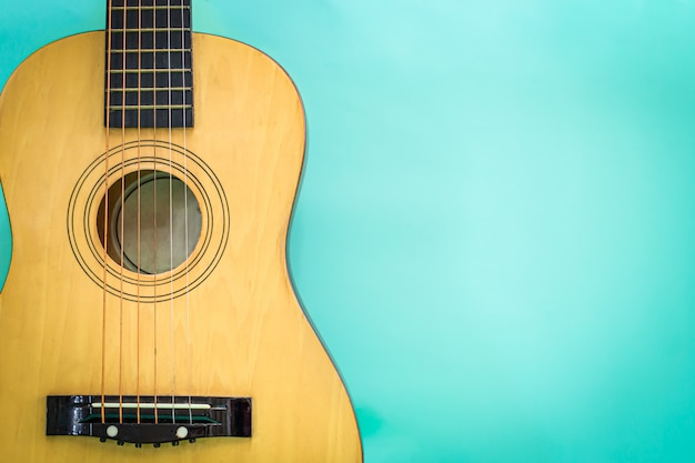 Acoustic guitar resting against a green background