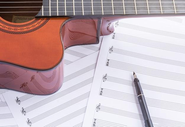 木製テーブル上のアコースティックギター、楽譜、万年筆