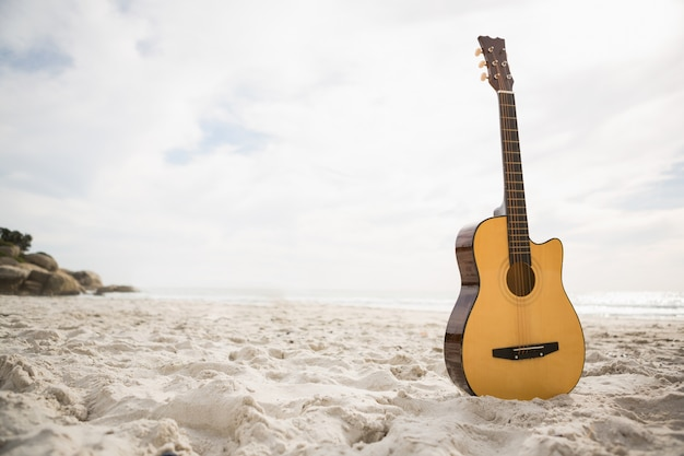 Acoustic guitar standing in the sand
