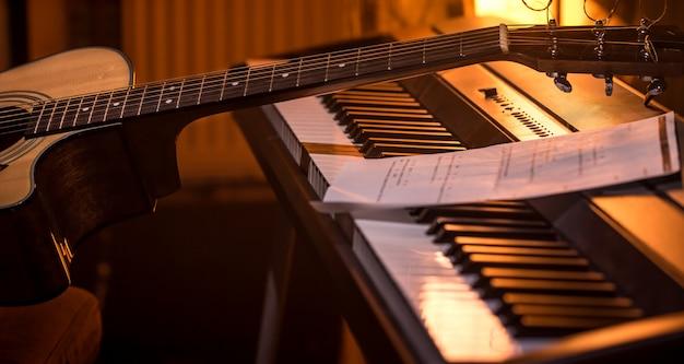 Акустическая гитара стоит на фортепиано с нотами, крупным планом