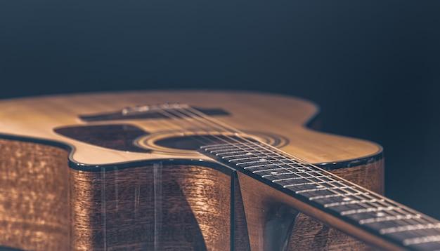 스포트라이트에 비추어 검정색 배경에 아름다운 나무가 있는 어쿠스틱 기타.
