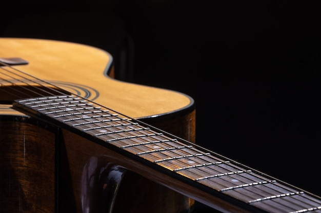 검정색 배경에 아름다운 나무가 있는 어쿠스틱 기타.