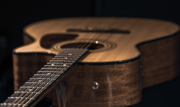 Acoustic guitar with a beautiful wood on a black background close-up.