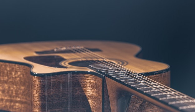 Acoustic guitar with a beautiful wood on a black background in the light of a spotlight.