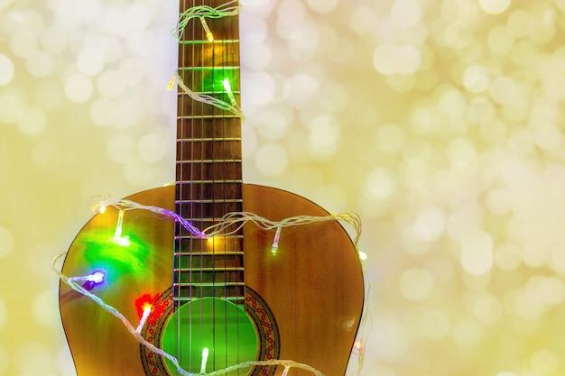 ボケ味のあるカラフルな花輪に包まれたアコースティックギター。背景としてのクリスマスと新年の音楽ギフト