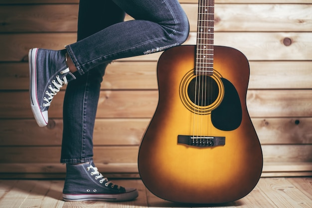 Acoustic six string light brown guitar and female legs in jeans with wooden wall background