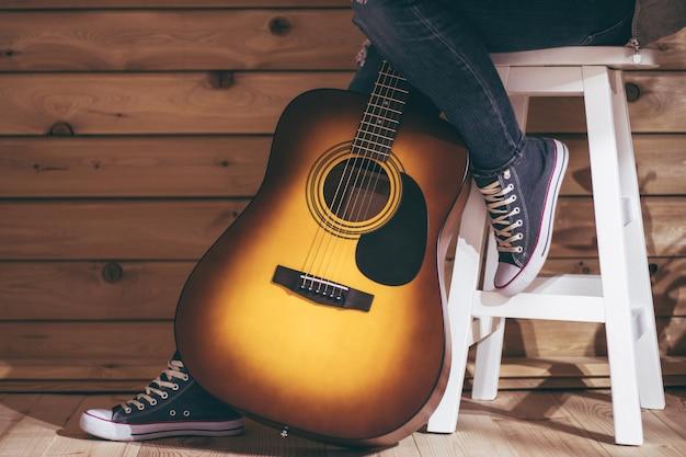 Акустическая шестиструнная желто-коричневая гитара и ноги женщины, сидящей на табурете в джинсах, у деревянной стены