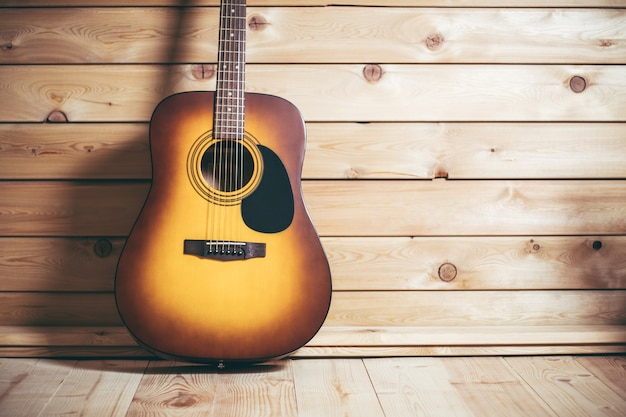 Acoustic six-stringed yellow-brown guitar standing near wooden wall. copy space.