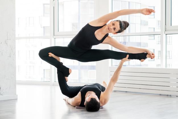 Красивый молодой мужчина и женщина практикуют пару упражнений йоги acro в белой фитнес-студии вместе с большими окнами