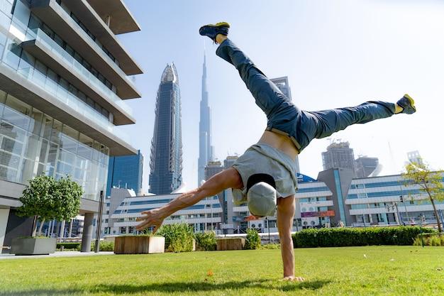 Acrobat удерживает равновесие на одной руке с размытым городским пейзажем дубая