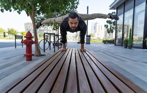 Акробат держит равновесие руками на улице