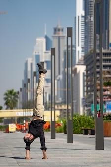 Acrobat удерживает равновесие в руках на фоне размытого городского пейзажа дубая. концепция современных, деловых и неограниченных возможностей.