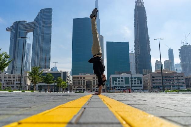 Acrobat сохраняет равновесие в руках на размытом городском пейзаже дубая