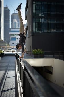Acrobat сохраняет равновесие в руках на размытом городском пейзаже дубая Premium Фотографии