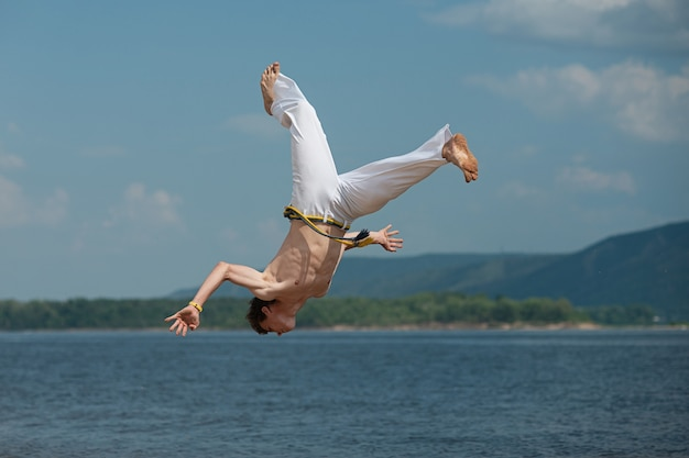 Acrobat performs an acrobatic trick, somersault on the beach.