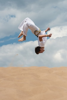 Acrobat performs an acrobatic trick, somersault on the beach